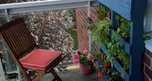 vertical-blue-pallet-garden-bricks-wall-wooden-armchair-cushion-flower-pots