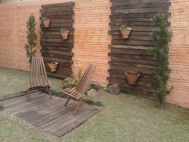 vertical garden pallet wooden slats varnished armchairs flower pots bricks wall backyard lawn