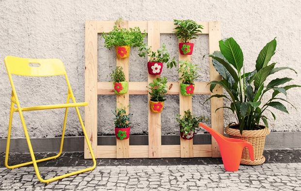 vertical pallet garden decorated flower pots white wall yellow chair paver