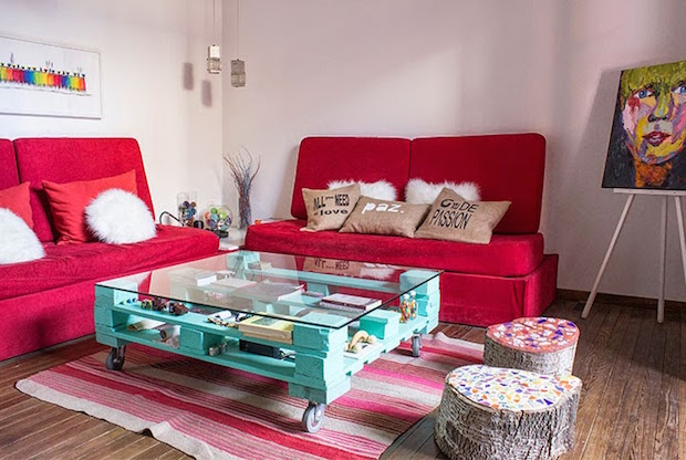 creative coloured pallet table glass storage bookshelves red sofa white fluffy cushions woollen carpet tree logs upcycled stools