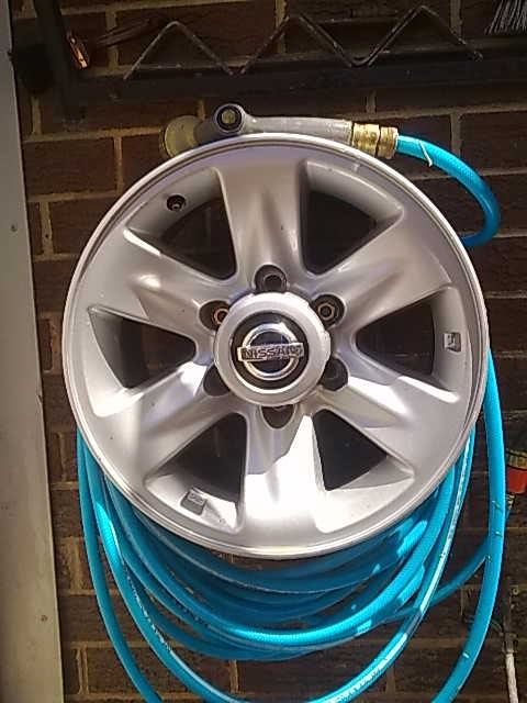 reused car rims upcycled garden hose holder wall hanging craft